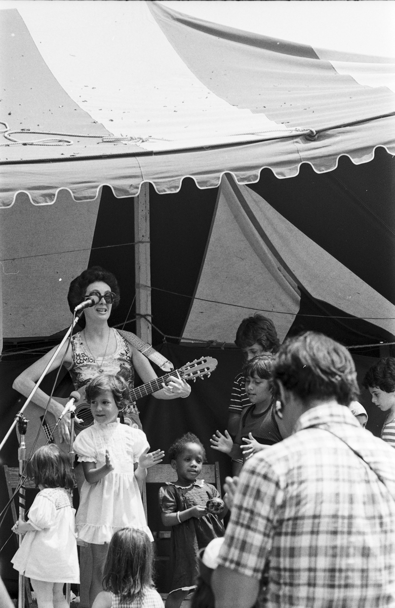 Photograph of Lois Lilienstein performing at Mariposa Folk Festival, surrounded by children.