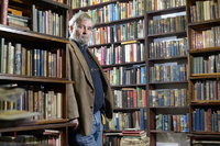 David Mason Leaning on a book Shelf